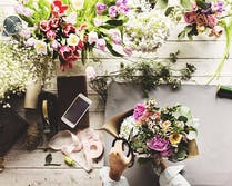 Various flowers, plants and accents atop a wooden workbench