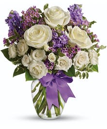 Lovely white and purple floral bouquet in a perfect glass vase, and finished with a purple ribon.