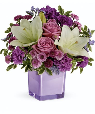 These luxurious lavender roses and crisp white lilies are poised to please. Perfectly presented in a stylish cube vase.